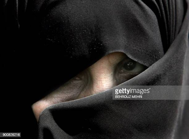 An Iranian woman covers her face attending a demonstration to protest against women who violate the strict Islamic dresscode after the Friday prayers...