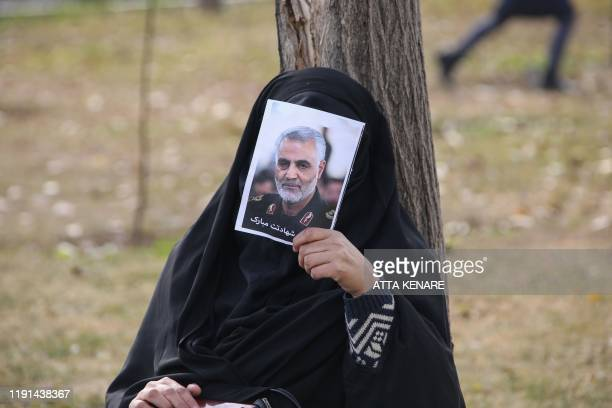 An Iranian woman covers her face with a picture of Iranian Revolutionary Guards Major General Qasem Soleimani during a demonstration in Tehran on...
