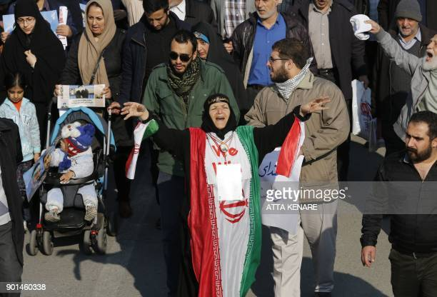 An Iranian woman dressed in the colours of the national flag shouts slogans during a progovernment march held after the weekly Friday prayers in...