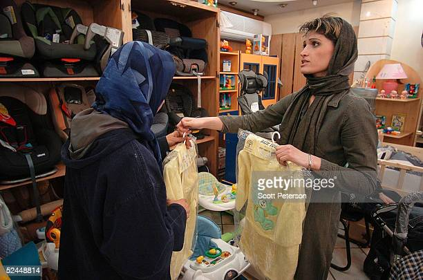 An Iranian woman helps another Iranian woman to choose baby clothes in the store before the forthcoming Iranian New Year of Norouz March 18 2004 in...