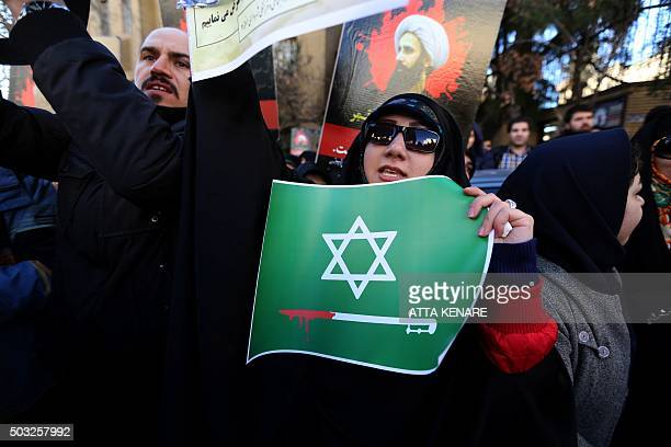 An Iranian woman holding a placard takes part in a demonstration outside the Saudi embassy in Tehran on January 3 against the execution of prominent...