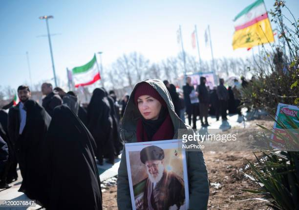 An Iranian woman holds a portrait of Irans Supreme Leader Ayatollah Ali Khamenei while taking part a rally to mark the Islamic Revolution anniversary...