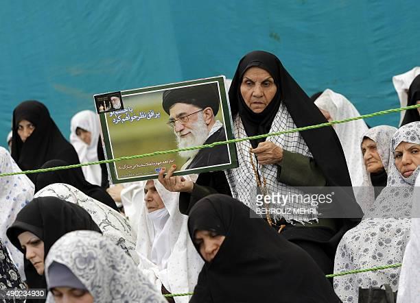 An Iranian woman holds a portrait of Iran's supreme leader Ayatollah Ali Khamenei during the weekly Friday prayers at Tehran University on July 3...