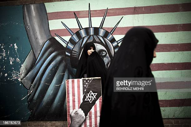 An Iranian woman holds an antiUS poster as she stands in front of a mural of the Statue of Liberty bearing the face of a skull on the wall of the...