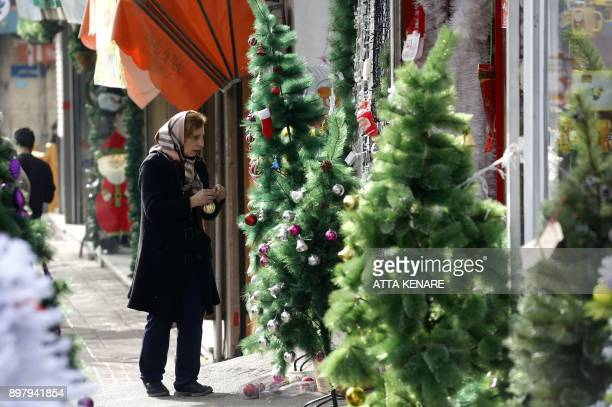An Iranian woman holds Christmas decorations next to a tree on a street in the capital Tehran on December 24 on Christmas eve / AFP PHOTO / ATTA...