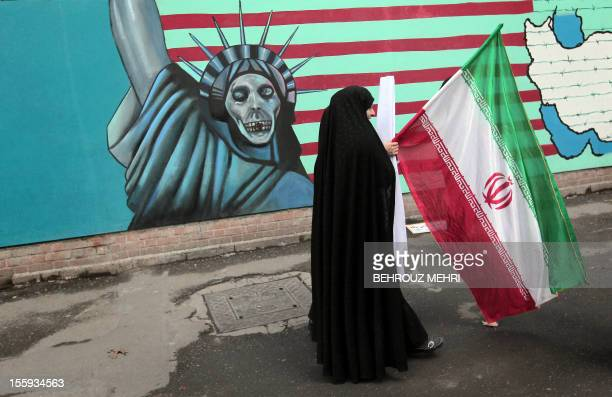 An Iranian woman holds her national flag as she walks past an antiUS mural depicting the Statue of Liberty on the wall of the former US embassy in...