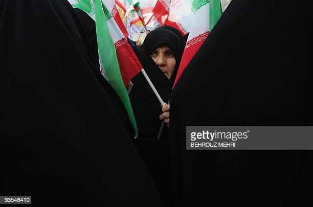 An Iranian woman holds her national flag during a rally outside the former US embassy in Tehran on November 4 2009 to mark the storming of the...