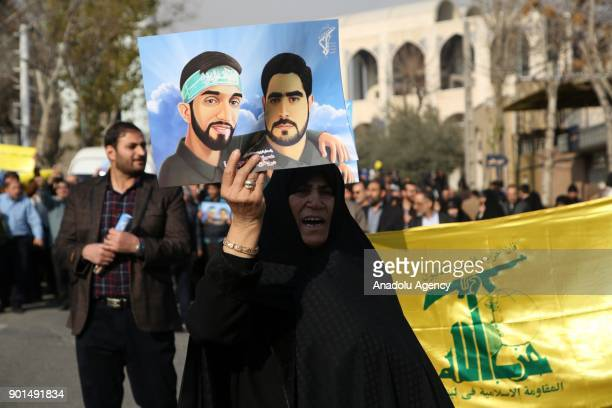 An Iranian woman holds placard during a protest after performing the Friday Prayer at Imam Khomeini Mosque following US' statement about backing the...