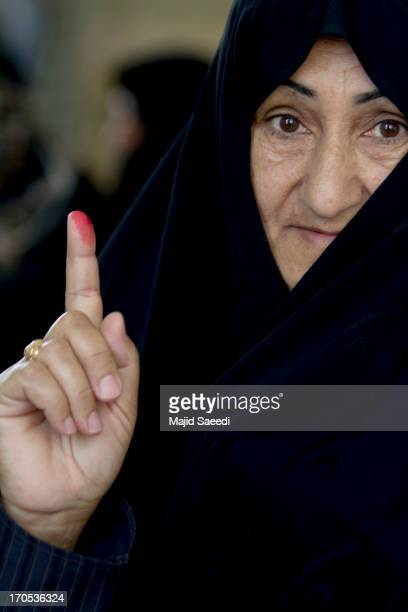 An Iranian woman holds up her inked finger after casting her vote at a polling station during the first round of the presidential election on June 14...