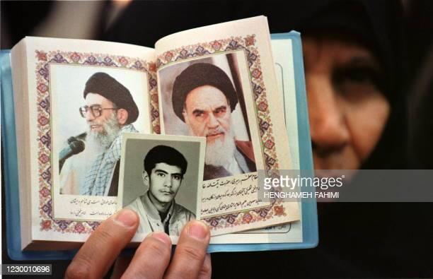 An Iranian woman holds up portraits Iran's supreme leader Ayatollah Ali Khamenei , his predecessor Ayatollah Ruhollah Khomeini, and her son, who was...