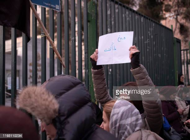 An Iranian woman holdsup a placard with a Persian script that reads The lie killed us as she attends in front of a University to mark the memory of...