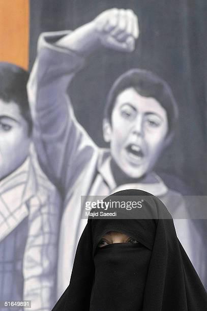 An Iranian woman is pictured in front of an antiUS mural outside the former US Embassy at a gathering to mark the 25th anniversary of the seizure of...