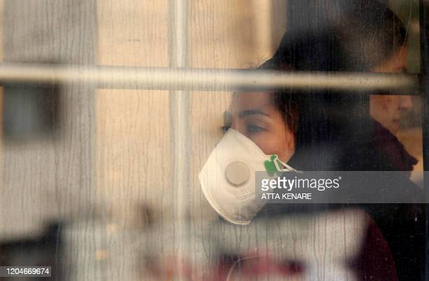 An Iranian woman is pictured wearing a protective mask while riding a bus in the Iranian capital Tehran on March 2 following the COVID-19 illness...