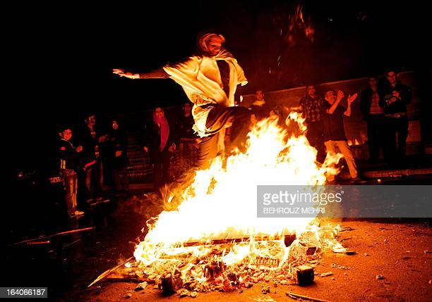 An Iranian woman jumps over a bonfire in southern Tehran on March 19 2013 during the Wednesday Fire feast or Chaharshanbeh Soori held annually on the...