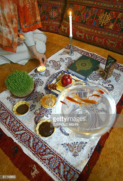 An Iranian woman lights a candle of the traditional decorated Haft Seen or Seven S on the first day of the Iranian New Year 1383 or Norouz according...