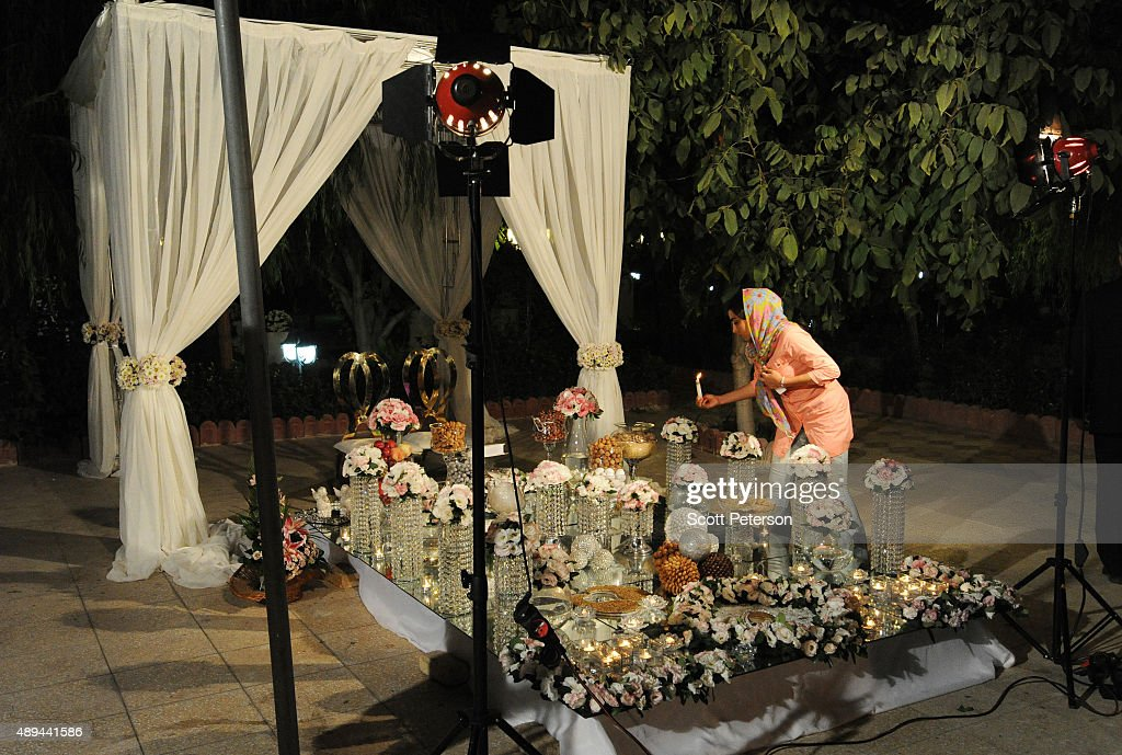 An Iranian woman lights candles on an elaborate table laid out with flowers and glass ornaments for a luxury wedding with mixed dancing and removal of headscarves, at a private garden tailor-made for the purpose west of Tehran, Iran, on September 14, 2015. Such weddings are booming business in Iran with an average price tag of $20,000, though they also often break Islamic rules and can be shut down by police if they do not have a permit.