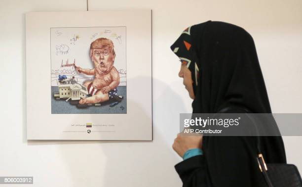 An Iranian woman looks at cartoons of US President Donald J Trump at an exhibition of the Islamic Republic's 2017 International Trumpism cartoon and...
