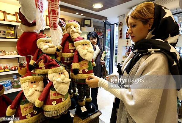 An Iranian woman looks at Christmas decorations at a shop in Tehran on December 23 as Christians around the world prepare to celebrate Christmas AFP...