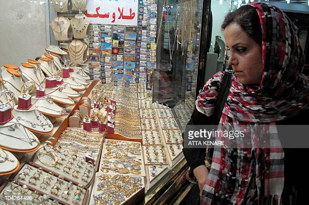 An Iranian woman looks at jewellery displayed in the window of a shop specialised in gold in central Tehran on September 20 as gold prices struck...