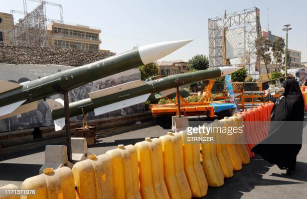 An Iranian woman looks at Taer2 missile during a street exhibition by Iran's army and paramilitary Revolutionary Guard celebrating Defence Week...