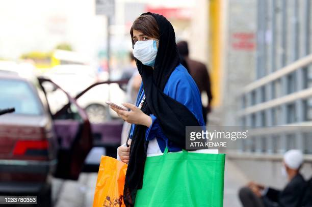 An Iranian woman, mask-clad due to the coronavirus pandemic, waits to cross a street in the capital Tehran, on July 3, 2021. - President Hassan...