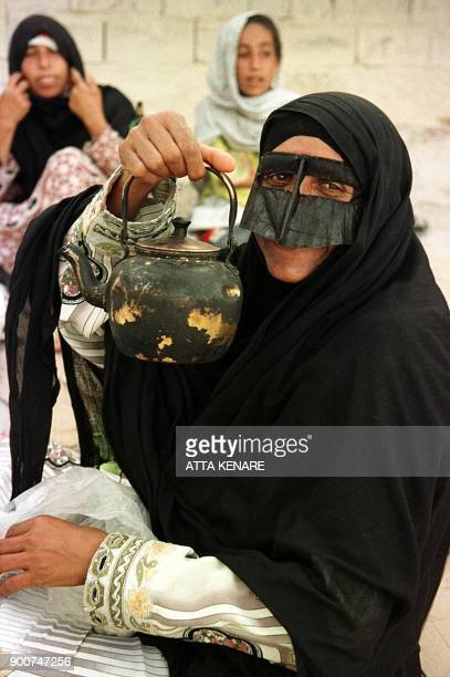 An Iranian woman native to Kish Island in the Persian Gulf holds up a teapot 21 May 2000 with her face covered by a 'burqa' typical of eastern Iran...