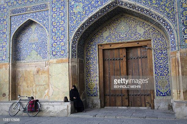 An Iranian woman observes prayers while sitting outside the Imam Khomeini mosque at the historical Naqsh-e Jahan Square in Isfahan on August 31, 2011...