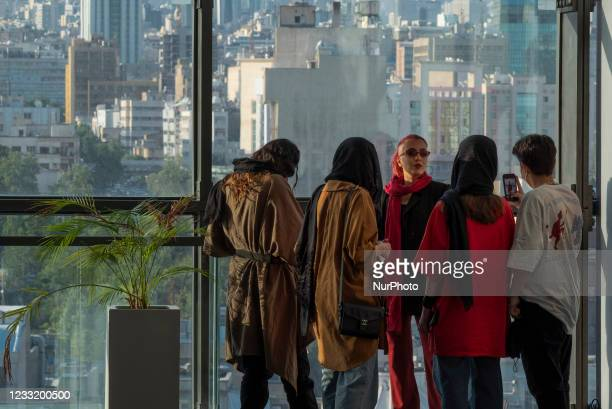 An Iranian woman poses as her friend takes a photograph with his smartphone while standing at a shopping mall in downtown Tehran on May 29, 2021....