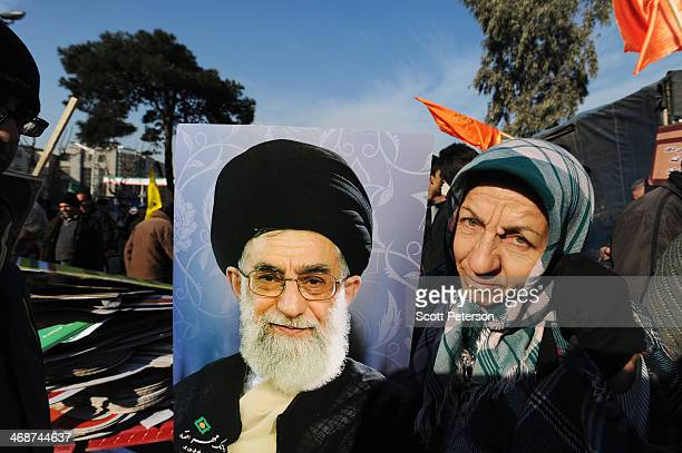 An Iranian woman poses with a portrait of Supreme Leader Ayatollah Ali Khamenei as Iranians stage a mass rally to mark the 35th anniversary of the...