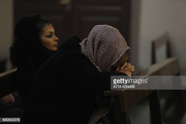 An Iranian woman prays as she attends Christmas Eve mass at the St Joseph Armenian Catholic church in Tehran on December 24 as Christians around the...