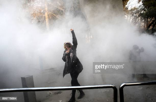 An Iranian woman raises her fist amid the smoke of tear gas at the University of Tehran during a protest driven by anger over economic problems, in...