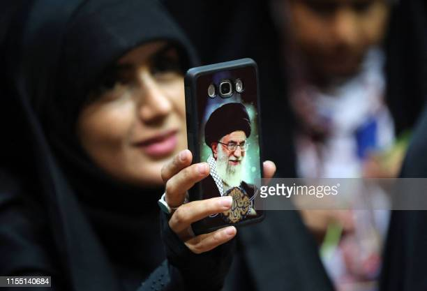 An Iranian woman shows her phone cover of Iran's Supreme Leader Ayatollah Ali Khamenei as she attends a rally in support of wearing headscarves at...