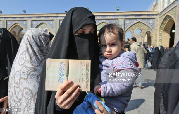 An Iranian woman shows her voting document during parliamentary elections at the Shah Abdul Azim shrine on the southern outskirts of Tehran on...