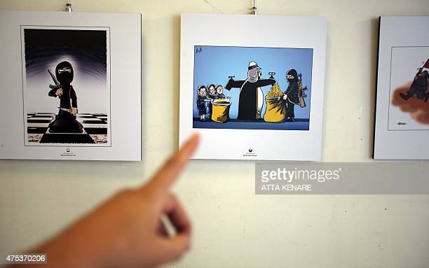 An Iranian woman shows the work of Moroccan cartoonist Benaji Naji during an exhibition as part of the Daesh International Cartoon and Caricature...