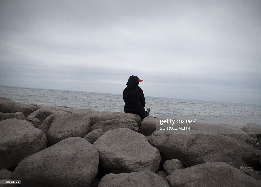An Iranian woman sits by the water in the Caspian Sea city of Tonekabon, 250 kms north of the capital Tehran, on May 21, 2010. The Caspian Sea is the world's largest lake with a surface area of 371,000 kms bounded by northern Iran, southern Russia, western Kazakhstan and Turkmenistan, and eastern Azerbaijan. Iran was preparing to notify the International Atomic Energy Agency later on May 24 of a nuclear fuel swap deal brokered by Turkey and Brazil, the spokesman of Iran's Atomic Energy Organisation said.