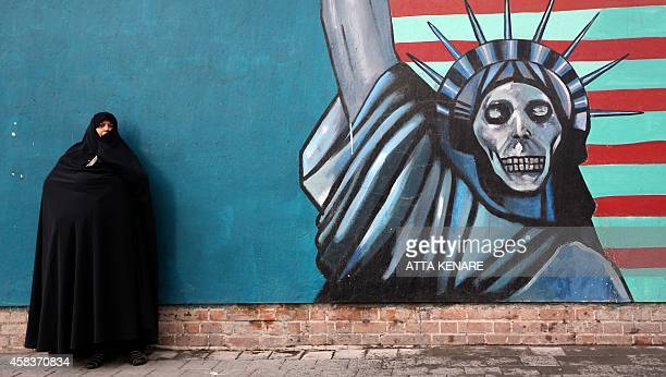 An Iranian woman stands in front of the painted wall of the former US embassy on November 4 2014 in Tehran where takes place a demonstration to mark...