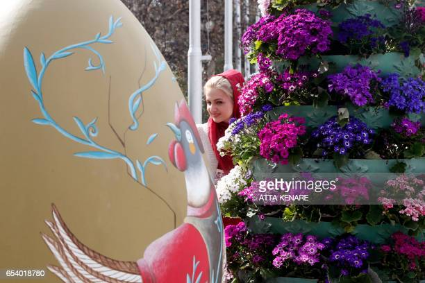 An Iranian woman takes a closer look at a large decorated egg displayed at the Mellat park during an event organised by the municipality of Tehran on...