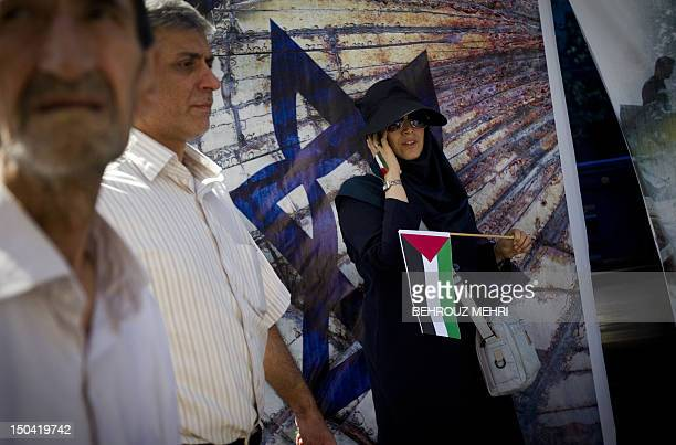 An Iranian woman talks on her mobile phone as she holds a Palestinian flag in front of a picture of a the Jewish Star of David symbol in a street...