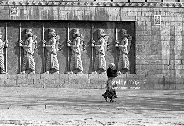 An Iranian woman walking in front of some of high relieves depicting a line of Persian guards. Tehran, 1956