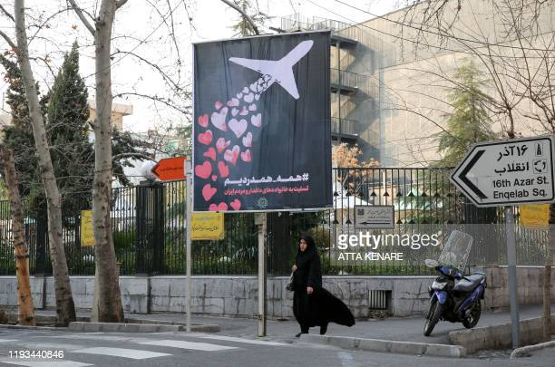 An Iranian woman walks beneath a poster honouring the victims of a Ukrainian passenger jet accidentally shot down in the capital last week, in front...