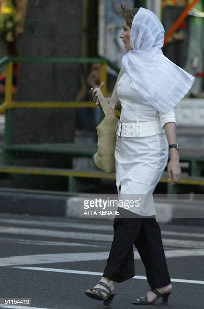 """An Iranian woman walks in a posh north Tehran shopping area 09 August 2004. The chief of Iran's police has told women not to dress up like """"models"""",..."""