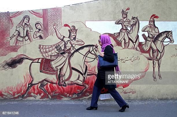 An Iranian woman walks in front of a mural in the Iranian capital Tehran on November 9 2016 / AFP / ATTA KENARE