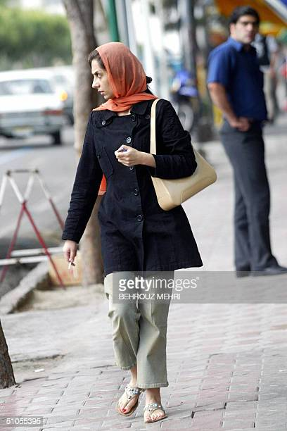 An Iranian woman walks in the northern rich area of Tehran 13 July 2004 A fresh crackdown by Iranian police targeting insufficiently veiled women has...