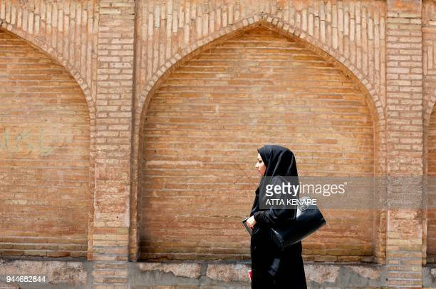 TOPSHOT An Iranian woman walks next to the 'SioSe Pol' bridge over the Zayandeh Rud river in Isfahan which now runs dry due to water extraction...