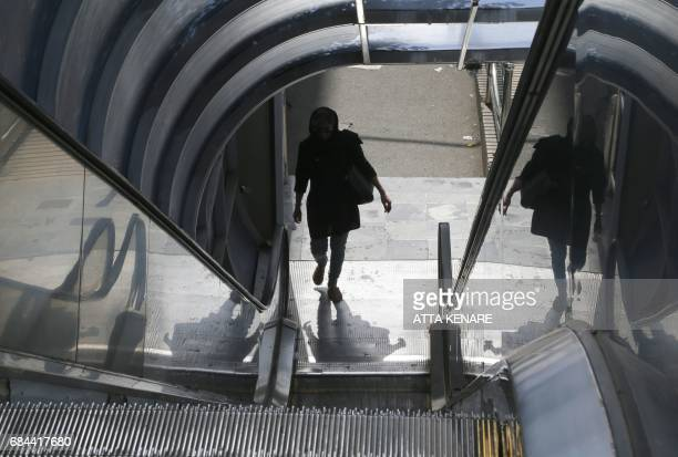 An Iranian woman walks onto an escalator in the capital Tehran on the eve of the presidential elections on May 18 2017 / AFP PHOTO / ATTA KENARE
