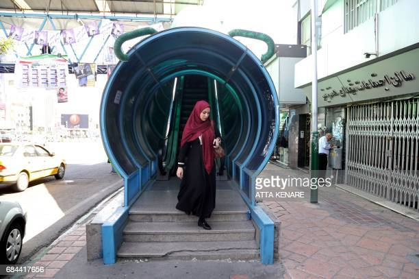 An Iranian woman walks out of a covered escalator in the capital Tehran on the eve of the presidential elections on May 18 2017 / AFP PHOTO / ATTA...