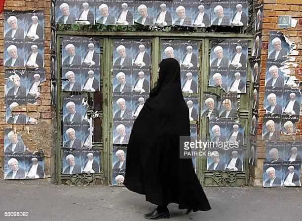 An Iranian woman walks part posters of pragmatic cleric Akbar Hasemi Rafsanjani in Tehran 18 June 2005 Iran's presidential election headed on...