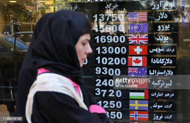 An Iranian woman walks past a currency exchange shop in the capital Tehran on April 24 2019 Iranians already hard hit by punishing US economic...