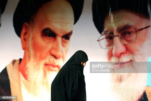 An Iranian woman walks past a giant poster showing supreme leader Ayatollah Ali Khamenei and the founder of Iran's Islamic Republic Ayatollah...