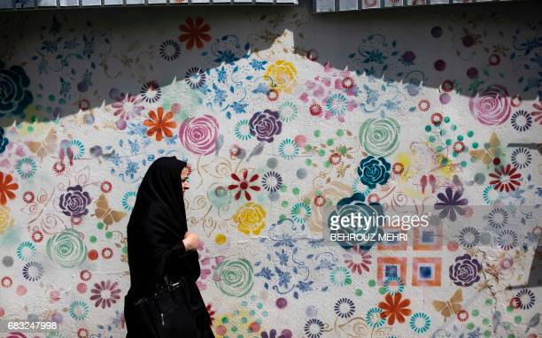 TOPSHOT An Iranian woman walks past a graffiti in Tehran on May 15 2017 After a series of bruising electoral defeats Iranian conservatives...